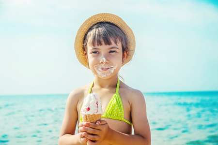 the child eats ice cream on the sea. Selective focus. summer. Stockfoto