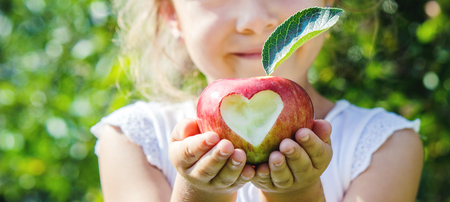 Child with an apple. Selective focus. Garden Food Stock Photo
