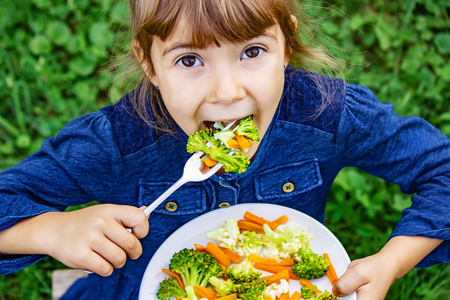 child eats vegetables. Summer photo. Selective focus nature Stockfoto