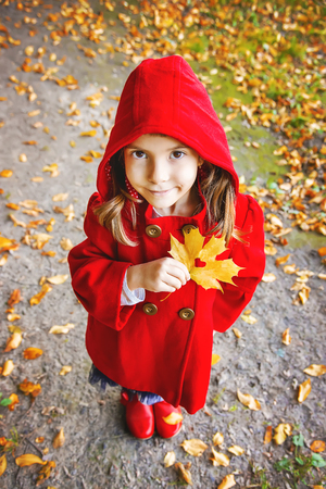 child in a red coat with autumn leaves. Love autumn. Selective focus. nature.