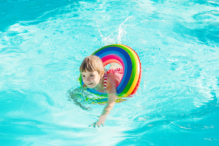 A child swims in a swimming pool with a life preserver. Selective focus.nature.