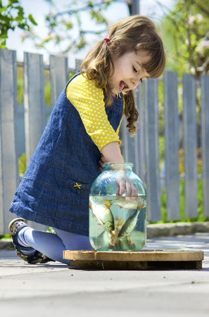 A child is playing with fish in a can. Selective focus.