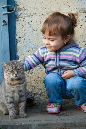 A child and a cat. Selective focus. Фото со стока