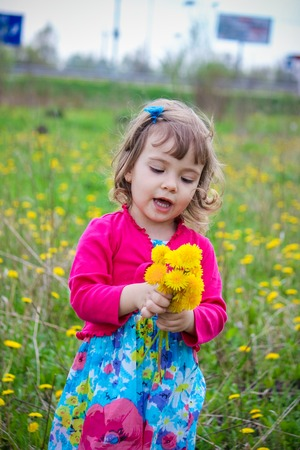 Girl, child, flowers in the spring plays. Selective focus.