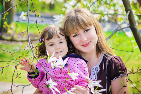 A child and mother in the blossoming magnolia garden. Stock Photo