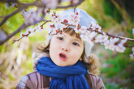 A child in a blooming garden. Selective focus.