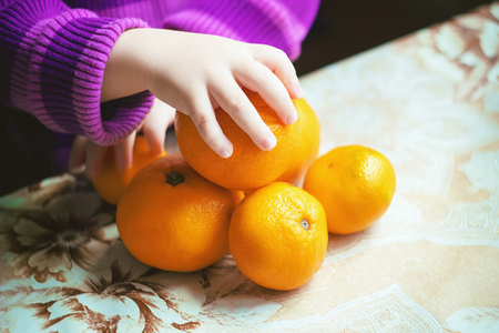 Child and tangerine. Selective focus. food and drink. 免版税图像