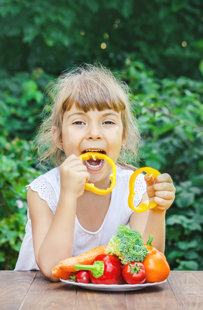 child eats vegetables. Summer photo. Selective focus nature Stock Photo