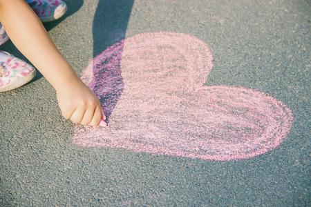the child paints chalk on the asphalt heart. Selective focus. Draw.