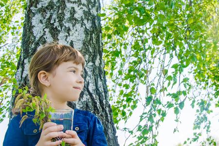 birch sap in the hands of a child. Selective focus. nature. Reklamní fotografie