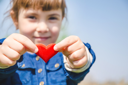The heart is in the hands of the child. Selective focus. nature.