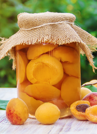 Preserved home-made apricots in jars. Selective focus. Food. Banco de Imagens