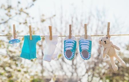 Babykleding en accessoires wegen op het touw na het wassen in de open lucht. Selectieve aandacht. natuur. Stockfoto