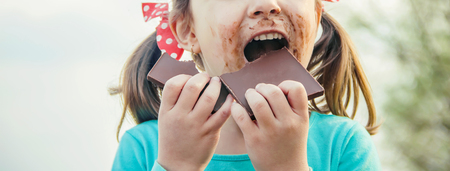 A sweet-toothed child eats chocolate. Selective focus. nature.