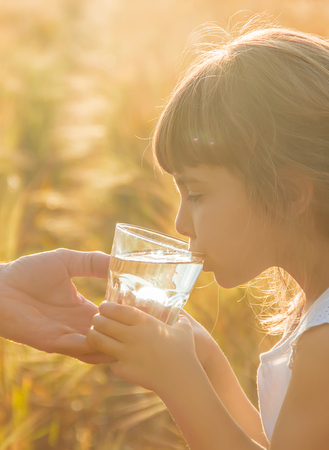 The father gives the child a glass of water. Selective focus. nature.