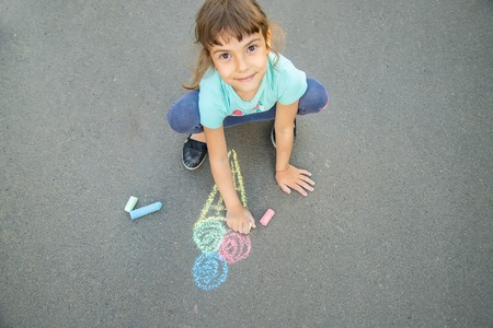 Child draws ice cream on asphalt with chalk. Selective focus. nature.