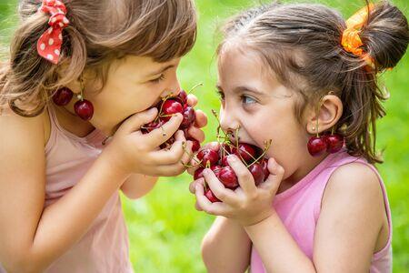 Los niños comen cerezas en verano. Enfoque selectivo.