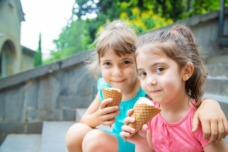 Children eat ice cream in the park. Selective focus.