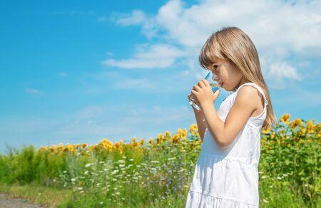 Un enfant boit de l'eau sur le fond du champ. Mise au point sélective. Banque d'images