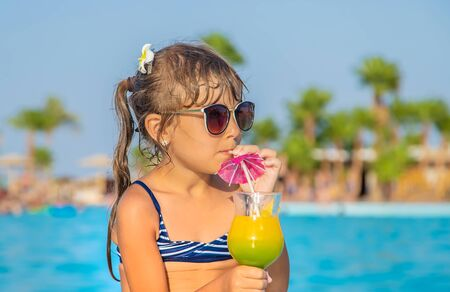 A child at the sea drinks a cocktail. Selective focus.