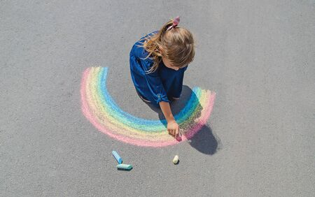 child draws with chalk on the pavement. Selective focus. Фото со стока