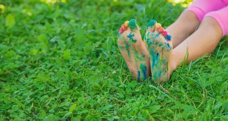 child with painted hands and legs. Selective focus. nature.