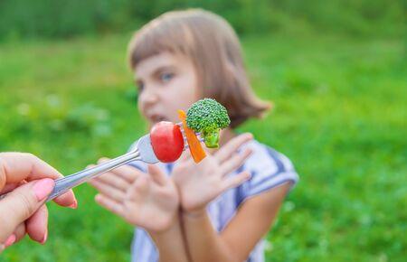 Kind isst Gemüse Brokkoli und Karotten. Selektiver Fokus.