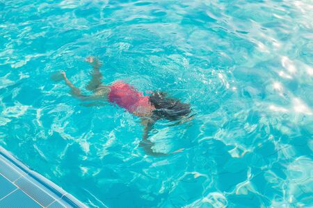 the child swims and dives in the pool. Selective focus. nature. Фото со стока - 129406395