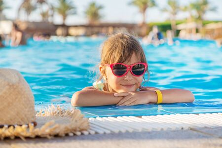 the child swims and dives in the pool. Selective focus. Stock fotó