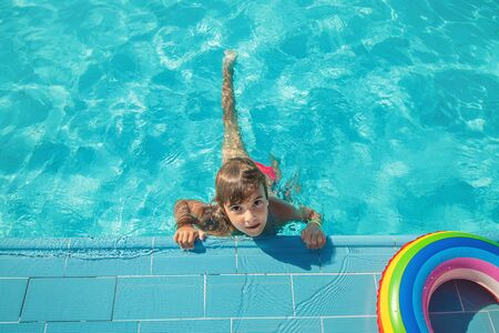 the child swims and dives in the pool. Selective focus. Фото со стока - 129409920