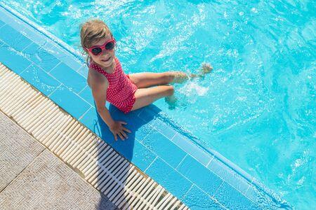 il bambino nuota e si tuffa in piscina. Messa a fuoco selettiva.