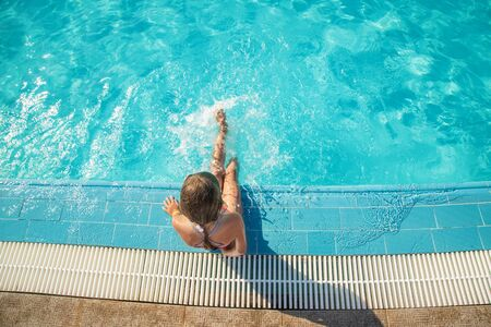 the child swims and dives in the pool. Selective focus. nature. Фото со стока - 129409923