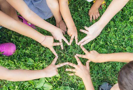 Kinderhände zusammen auf einem Hintergrund von Gras. Selektiver Fokus. Natur. Standard-Bild