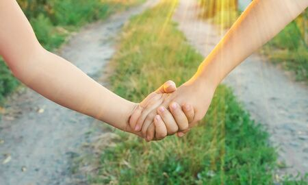 children hold hands together. Selective focus. nature. Фото со стока