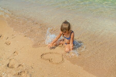 child draws in the sand on the beach. Selective focus. Banque d'images - 130536939
