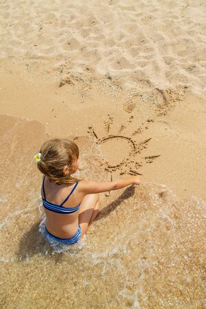 child draws in the sand on the beach. Selective focus. Banque d'images - 130536945