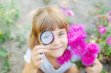 Child with a magnifying glass in his hands. Selective focus.