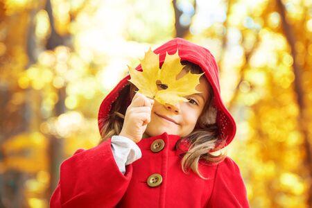 niño con un abrigo rojo con hojas de otoño. Amo el otoño. Enfoque selectivo.