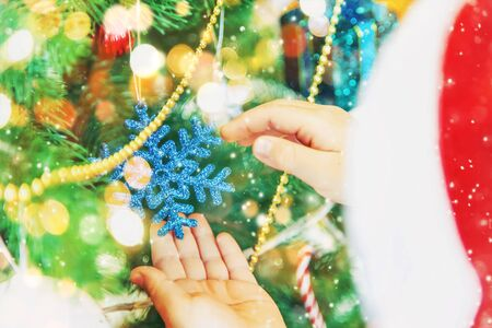 Christmas background and hands of a child with decorations. New Year. Selective focus. Holidays