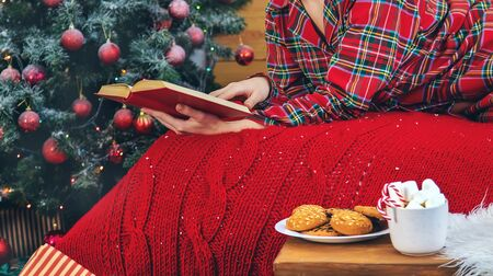 Christmas morning, girl in pajamas with a book. Selective focus. Holiday. Stock Photo