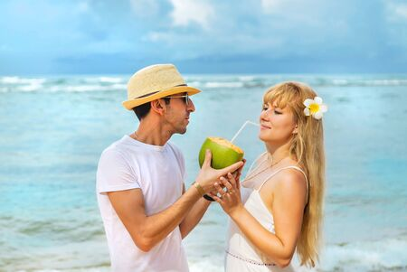 A man and a girl on the beach are drinking coconut. Selective focus.