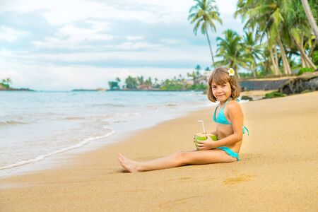 A child on the beach drinks coconut. Selective focus. Banque d'images - 138379273