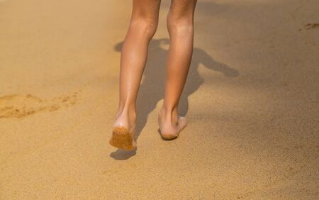 Feet of a child running along the beach. Selective focus. nature.