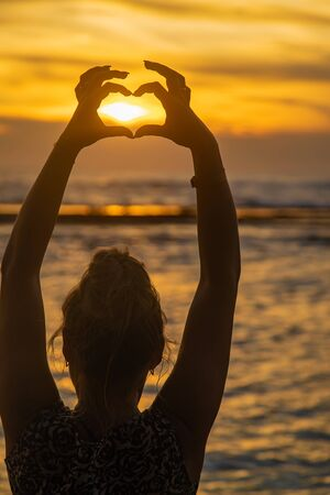 Girl makes heart hands at sunset. Sri Lanka. Selective focus. nature.