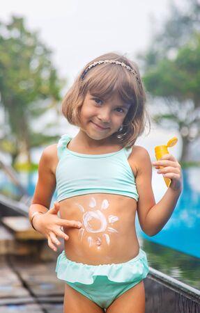 Kind am Strand mit Sonnencreme auf dem Rücken. Selektiver Fokus. Standard-Bild