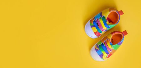 Shoes for newborns on a yellow background. Selective focus. Baby.