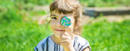 child eats lollipop on nature. Selective focus.