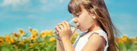A child drinks water on the background of the field. Selective focus.