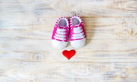 Baby booties and heart on a light background. Selective focus. nature.