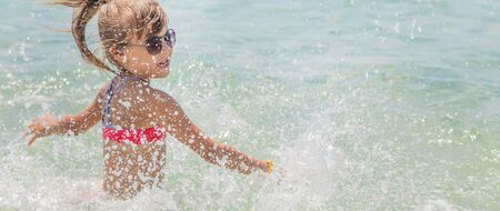 child makes spray on the sea. Selective focus.